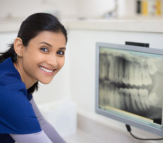 Dental team member looking at digital x-rays on computer